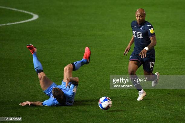 Kyle McFadzean of Coventry City goes to ground as Andre Ayew of Swansea City runs with the ball during the Sky Bet Championship match between...