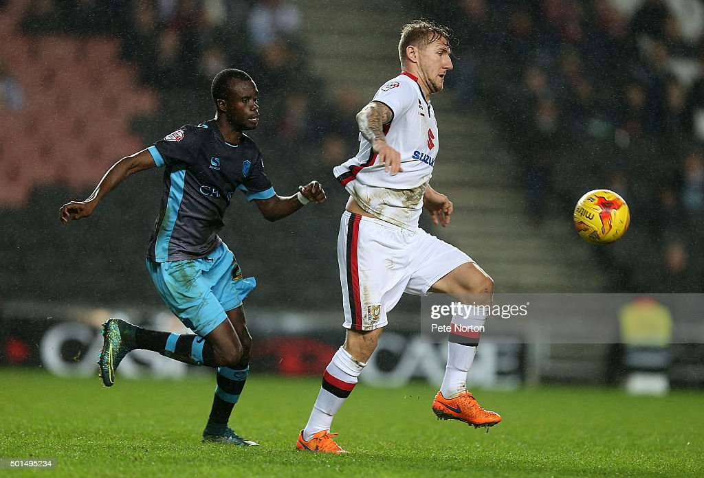 Kyle McFadzean of Milton Keynes Dons looks to play the ball watched by Modou Sougou of Sheffield Wednesday during the Sky Bet Championship match between Milton Keynes Dons and Sheffield Wednesday at stadium:mk on December 15, 2015 in Milton Keynes, United Kingdom.