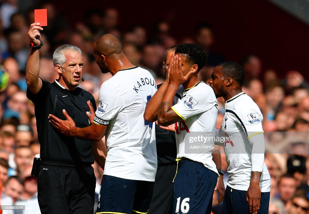 Kyle Naughton of Spurs reacts after receiving a red card for handball as Younes Kaboul of Spurs remenstrates with referee Chris Foy during the Barclays Premier League match between West Ham United and Tottenham Hotspur at Boleyn Ground on August 16, 2014 in London, England.