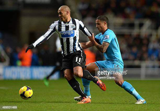 Kyle Naughton of Tottenham Hotspur holds onto Yoan Gouffran of Newcastle United during the Barclays Premier League match between Newcastle United and...