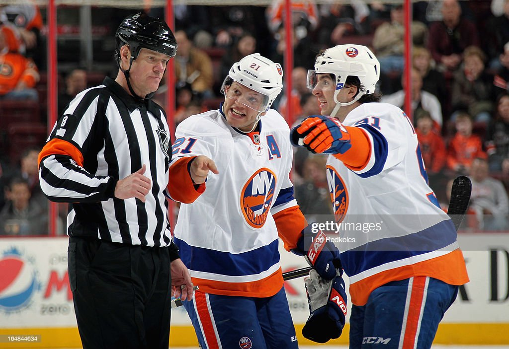 Kyle Okposo #21 and John Tavares #91 of the New York Islanders gesture to referee Dave Jackson #8 in the third period during a stoppage in the action against the Philadelphia Flyers on March 28, 2013 at the Wells Fargo Center in Philadelphia, Pennsylvania. The Islanders won 4-3 in a shootout.