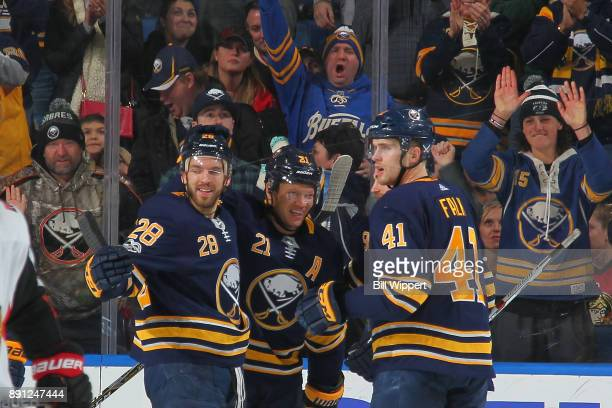 Kyle Okposo of the Buffalo Sabres celebrates his second period goal against the Ottawa Senators with teammates Zemgus Girgensons and Justin Falk...