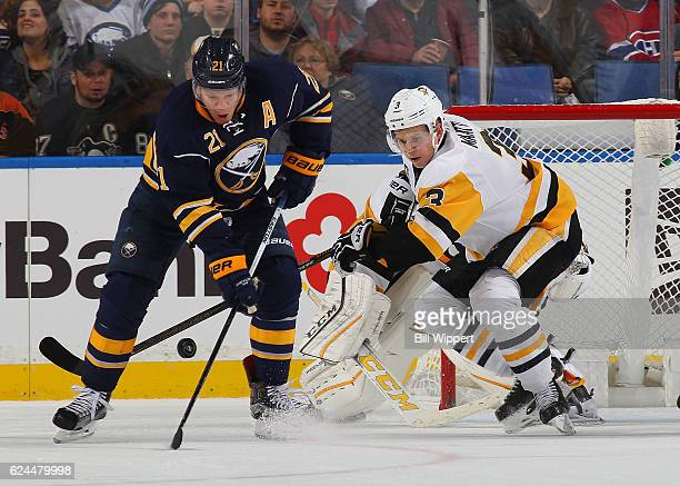 Kyle Okposo of the Buffalo Sabres for the puck against Olli Maatta of the Pittsburgh Penguins during an NHL game at the KeyBank Center on November 19...