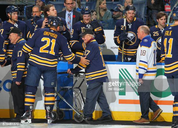 Kyle Okposo of the Buffalo Sabres greets Korean War Veteran Richard E Costo as former Sabre Danny Gare follows on Military Appreciation Night before...