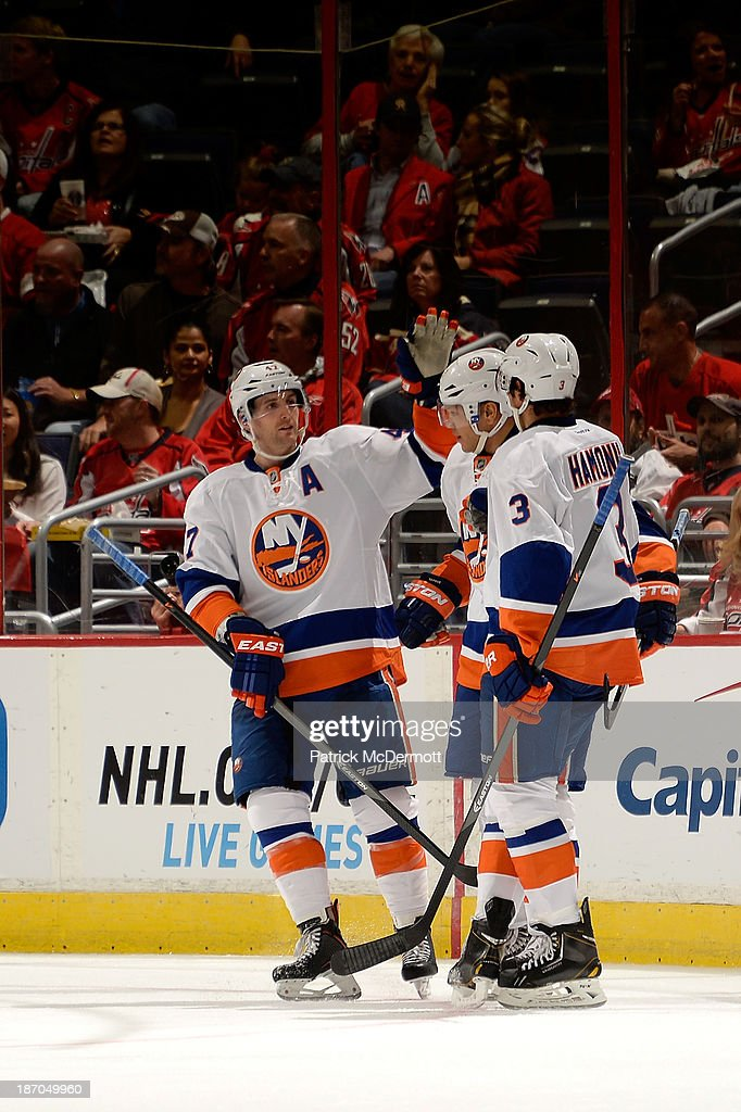 Kyle Okposo #21 of the New York Islanders celebrates with Andrew MacDonald #47 and Travis Hamonic #3 after scoring a goal in the second period during an NHL game against the Washington Capitals at Verizon Center on November 5, 2013 in Washington, DC.