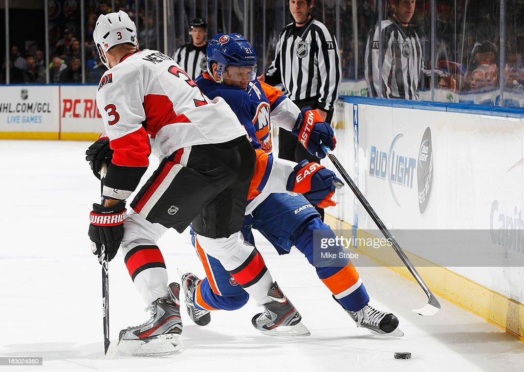 Kyle Okposo #21 of the New York Islanders handles the puck behind Marc Methot #3 of the Ottawa Senators at Nassau Veterans Memorial Coliseum on March 3, 2013 in Uniondale, New York. The Islanders defeated the Senators 3-2 in a shootout.