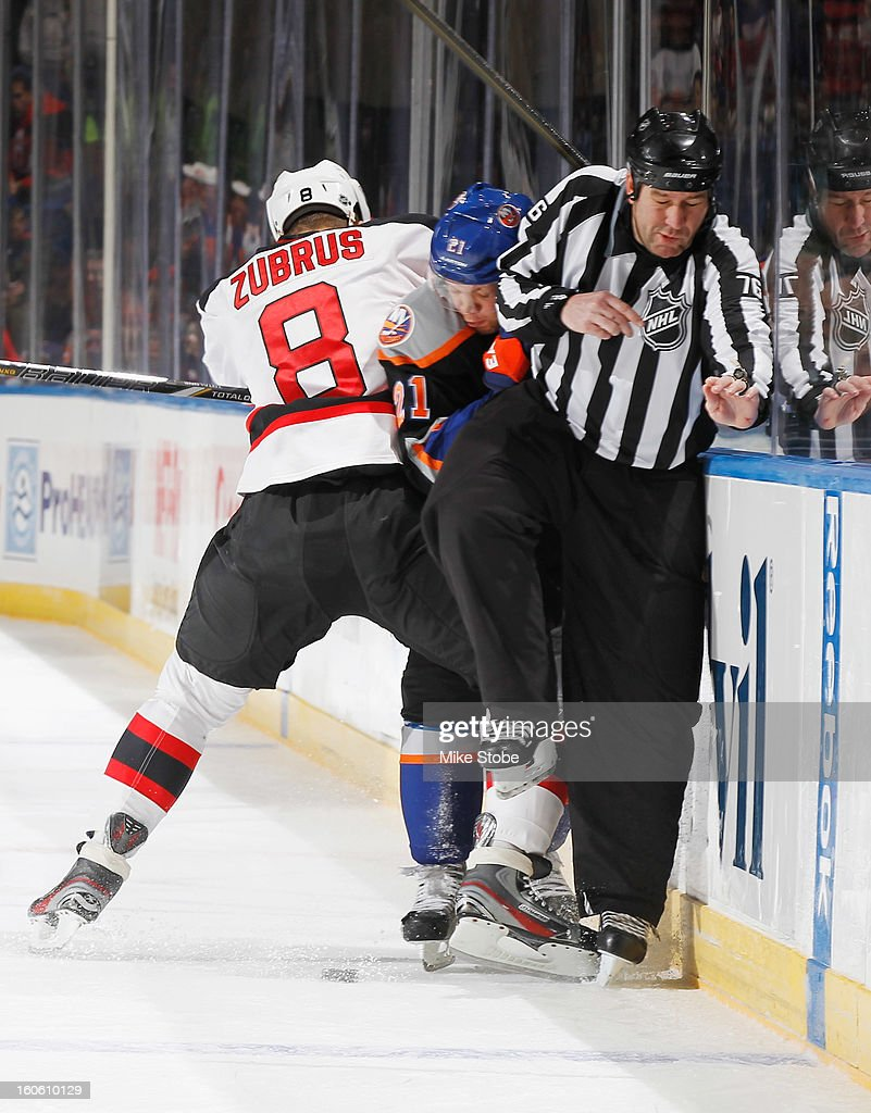 Kyle Okposo #21 of the New York Islanders is checked into the boards by Dainius Zubrus #8 of the New Jersey Devils in front of Linesman Michel Cormier #76 at Nassau Veterans Memorial Coliseum on February 3, 2013 in Uniondale, New York.