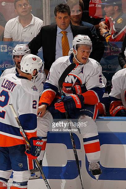 Kyle Okposo of the New York Islanders sits up on the boards with Head Coach Jack Capuano on the bench during a break in the action against the...