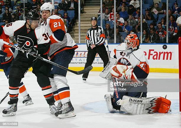 Kyle Okposo of the New York Islanders ties up Darroll Powe of the Philadelphia Flyers as goaltender Martin Biron of the Islanders makes the save on...