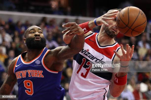 Kyle O'Quinn of the New York Knicks battles Marcin Gortat of the Washington Wizards for a rebound during the first half at Capital One Arena on...