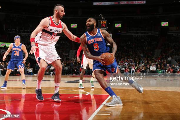 Kyle O'Quinn of the New York Knicks handles the ball against Marcin Gortat of the Washington Wizards on January 3 2018 at Capital One Arena in...