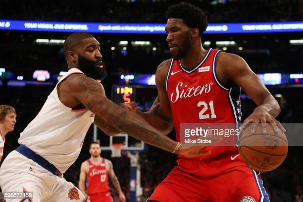 Kyle O'Quinn of the New York Knicks reacts defends against Joel Embiid of the Philadelphia 76ers at Madison Square Garden on December 25 2017 in New...