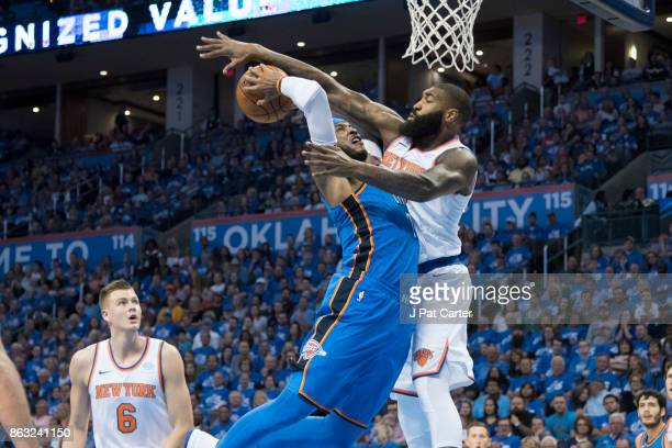 Kyle O'Quinn of the New York Knicks tries to block Carmelo Anthony of the Oklahoma City Thunder from shooting during the first half of a NBA game at...