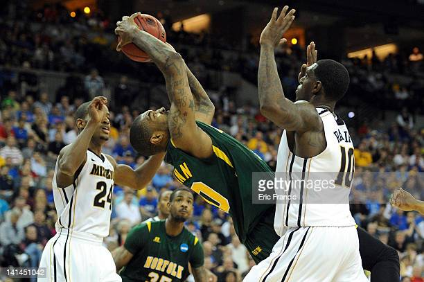 Kyle O'Quinn of the Norfolk State Spartans attempts to keep his balance under the basket against Kim English and Ricardo Ratliffe of the Missouri...