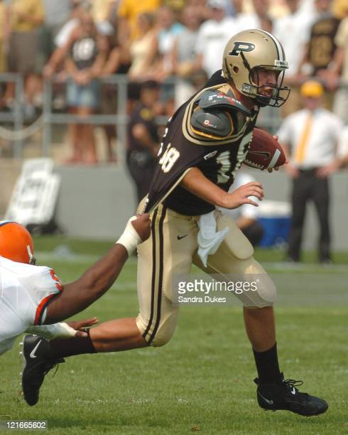Kyle Orton of Purdue scrambles up field in the third quarter as Tony Jenkins of Syracuse tries to hang on during the 51-0 defeat of Syracuse at...