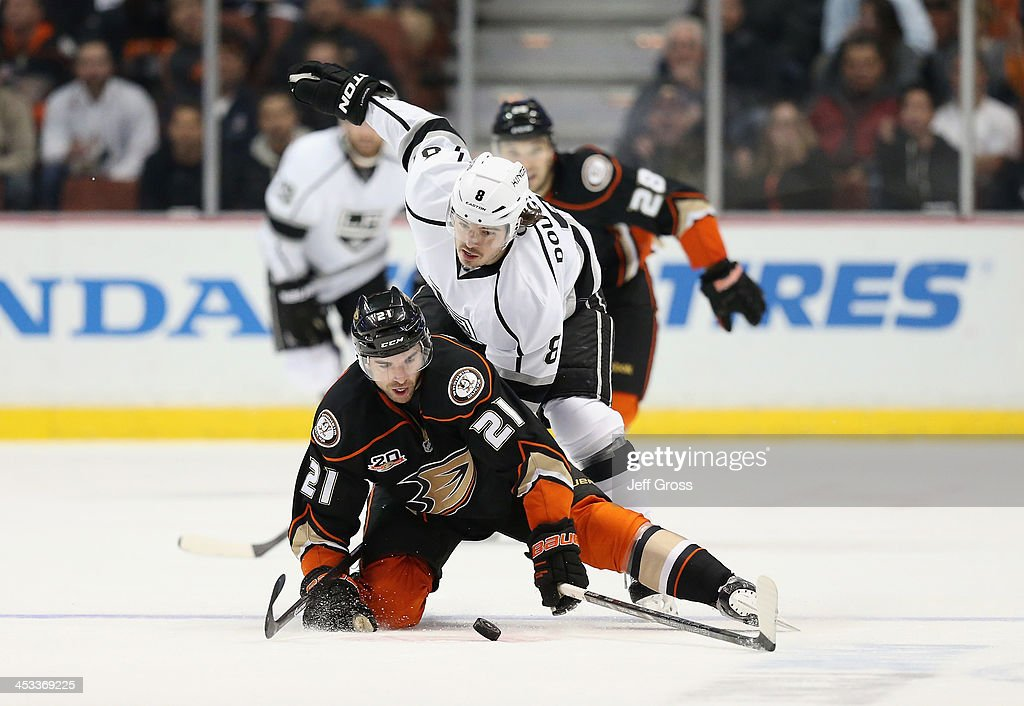 Kyle Palmieri #21 of the Anaheim Ducks and Drew Doughty #8 of the Los Angeles Kings fight for the puck in the first period at Honda Center on December 3, 2013 in Anaheim, California.