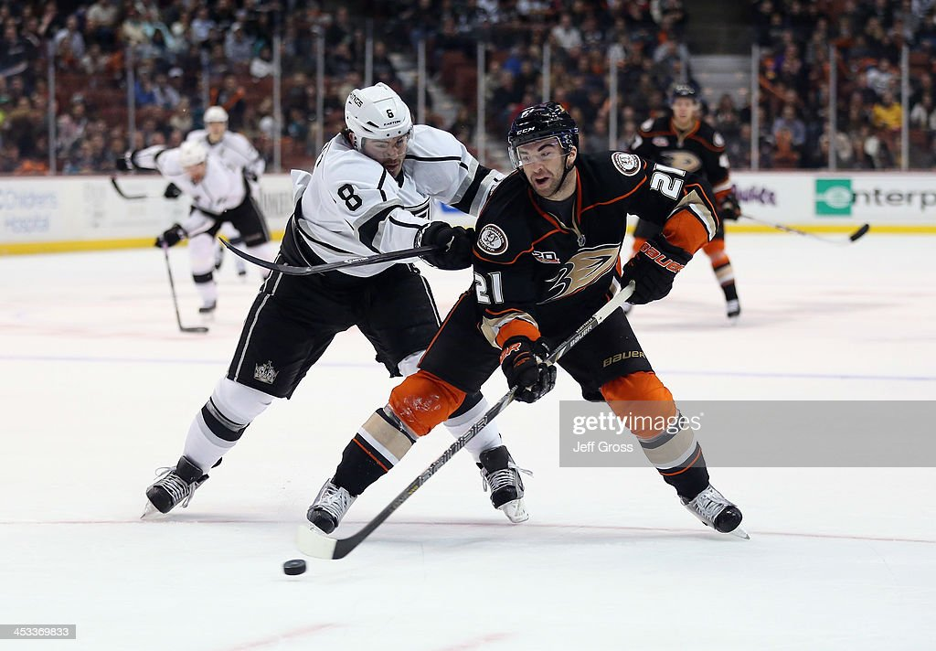 Kyle Palmieri #21 of the Anaheim Ducks is checked by Drew Doughty #8 of the Los Angeles Kings in the first period at Honda Center on December 3, 2013 in Anaheim, California.