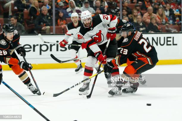 Kyle Palmieri of the New Jersey Devils and Brian Gibbons of the Anaheim Ducks fight for control of the puck at Honda Center on December 09 2018 in...