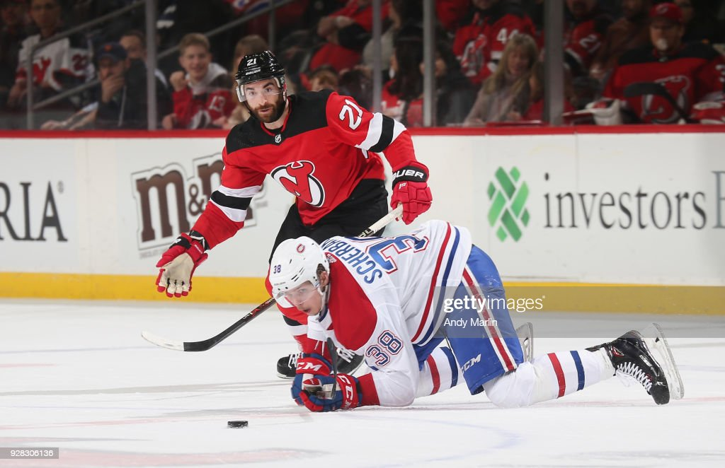Kyle Palmieri #21 of the New Jersey Devils and Nikita Scherbak #38 of the Montreal Canadiens battle for a loose puck during the game at Prudential Center on March 6, 2018 in Newark, New Jersey.