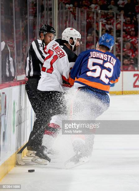 Kyle Palmieri of the New Jersey Devils and Ross Johnston of the New York Islanders come together near the boards during the game at Prudential Center...