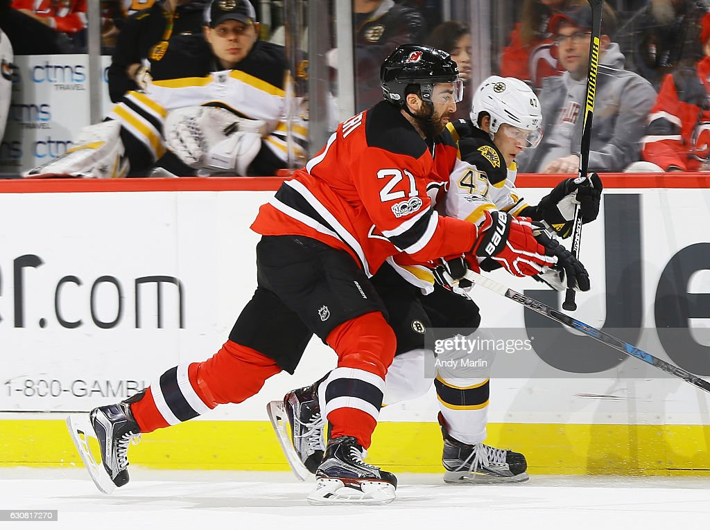 Kyle Palmieri #21 of the New Jersey Devils and Tory Krug #47 of the Boston Bruins battle for position during the game at Prudential Center on January 2, 2017 in Newark, New Jersey.