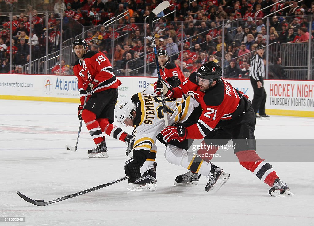 Kyle Palmieri #21 of the New Jersey Devils gets the stick on Lee Stempniak #20 of the Boston Bruins during the second period at the Prudential Center on March 29, 2016 in Newark, New Jersey.