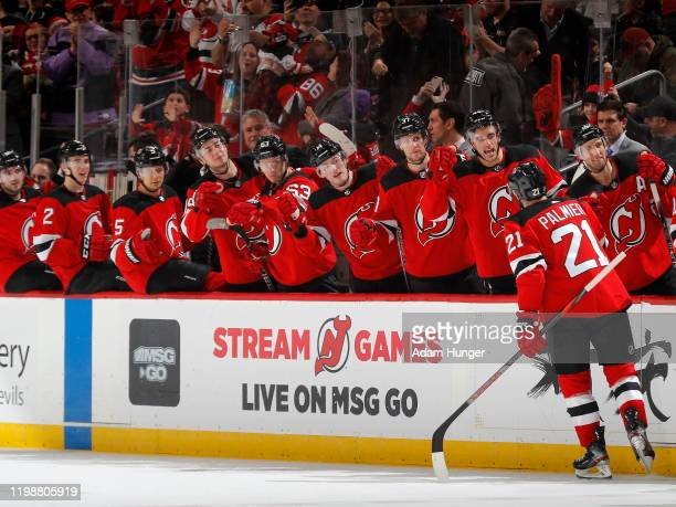 Kyle Palmieri of the New Jersey Devils is congratulated as he returns to the bench after scoring the gamy tying goal late in the third period against...