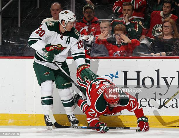 Kyle Palmieri of the New Jersey Devils is upended by Ryan Suter of the Minnesota Wild during the third period at the Prudential Center on March 17...