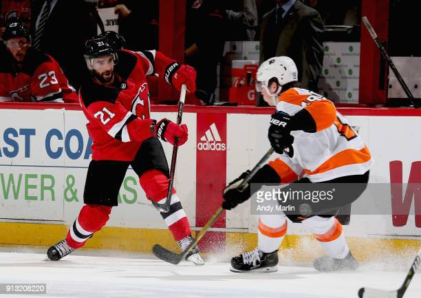 Kyle Palmieri of the New Jersey Devils plays the puck against Nolan Patrick of the Philadelphia Flyers during the game at Prudential Center on...