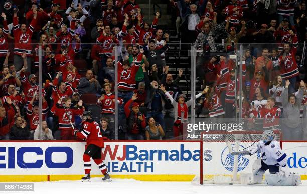 Kyle Palmieri of the New Jersey Devils reacts to scoring the game winning goal past Peter Budaj of the Tampa Bay Lightning during a shoot out at the...