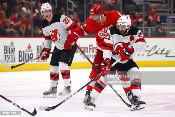 Kyle Palmieri of the New Jersey Devils tries to control the puck in front of Darren Helm of the Detroit Red Wings during the first period at Little...