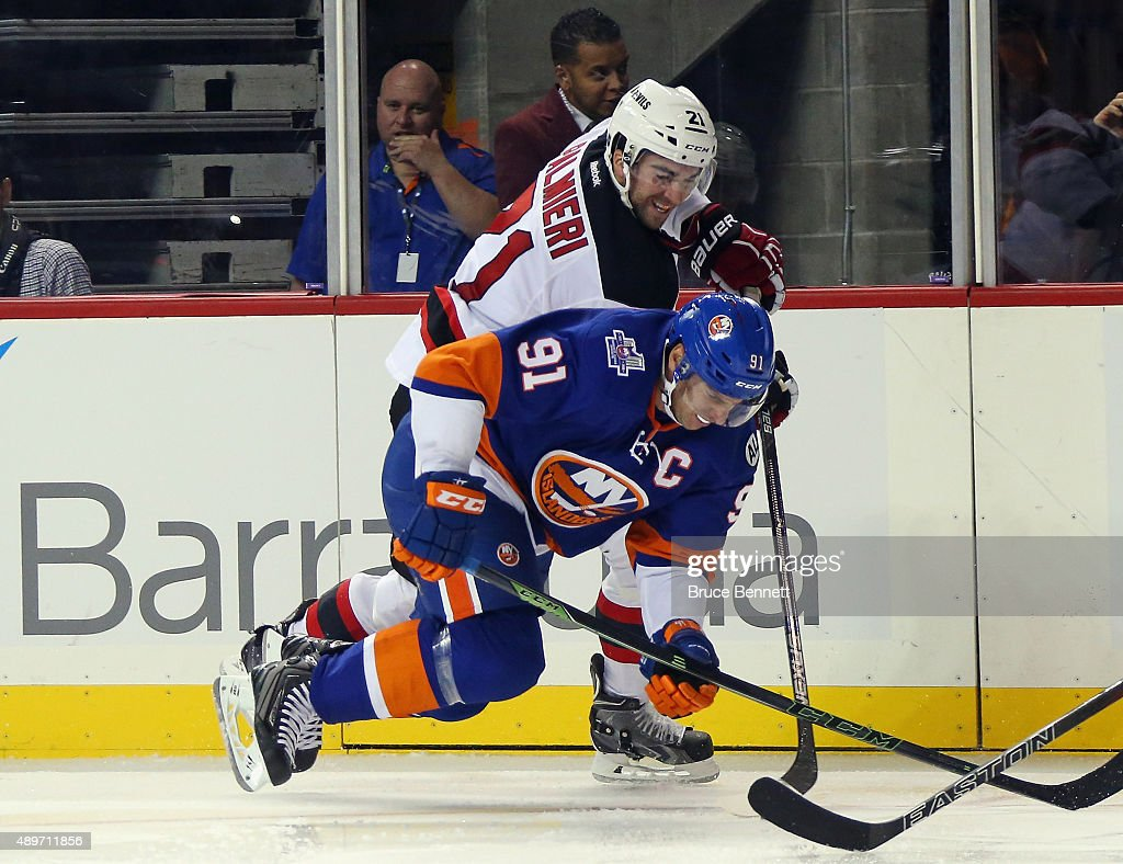 Kyle Palmieri #21 of the New Jersey Devils trips up John Tavares #91 of the New York Islanders during the second period at the Barclays Center on September 23, 2015 in the Brooklyn borough of New York City.