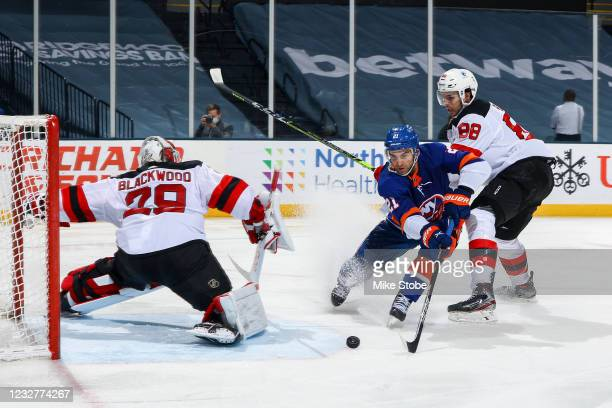 Kyle Palmieri of the New York Islanders scores a goal past Mackenzie Blackwood of the New Jersey Devils while defended by Kevin Bahl during the third...