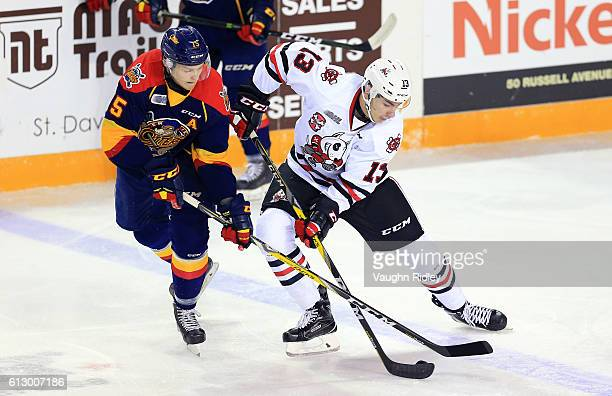 Kyle Petit of the Erie Otters and Graham Knott of the Niagara IceDogs battle for the puck during the first period of an OHL game at the Meridian...