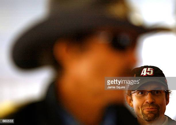 Kyle Petty driver of the Petty Enterprises Dodge Intrepid R/T looks on as his father Richard Petty talks with crew members during practice for the...