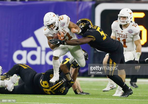 Kyle Porter of the Texas Longhorns leaps over AJ Logan of the Missouri Tigers as Jordan Harold attempts to make a tackle at NRG Stadium on December...
