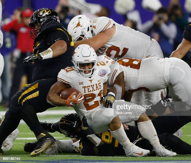Kyle Porter of the Texas Longhorns stumbles as he runs with the ball against the Missouri Tigers at NRG Stadium on December 27 2017 in Houston Texas