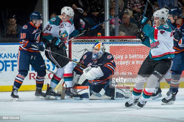 Kyle Pow of the Kelowna Rockets is checked by Nick Chyzowski as Dylan Ferguson of the Kamloops Blazers makes a first period save on December 27 2017...