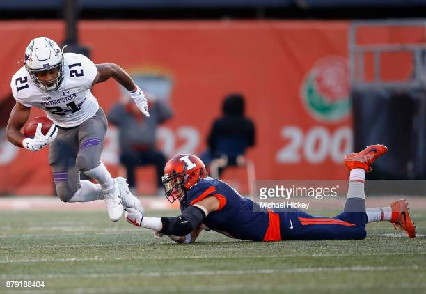 Kyle Queiro of the Northwestern Wildcats runs the ball as Bennett Williams of the Illinois Fighting Illini tries to make the shoestring tackle at...