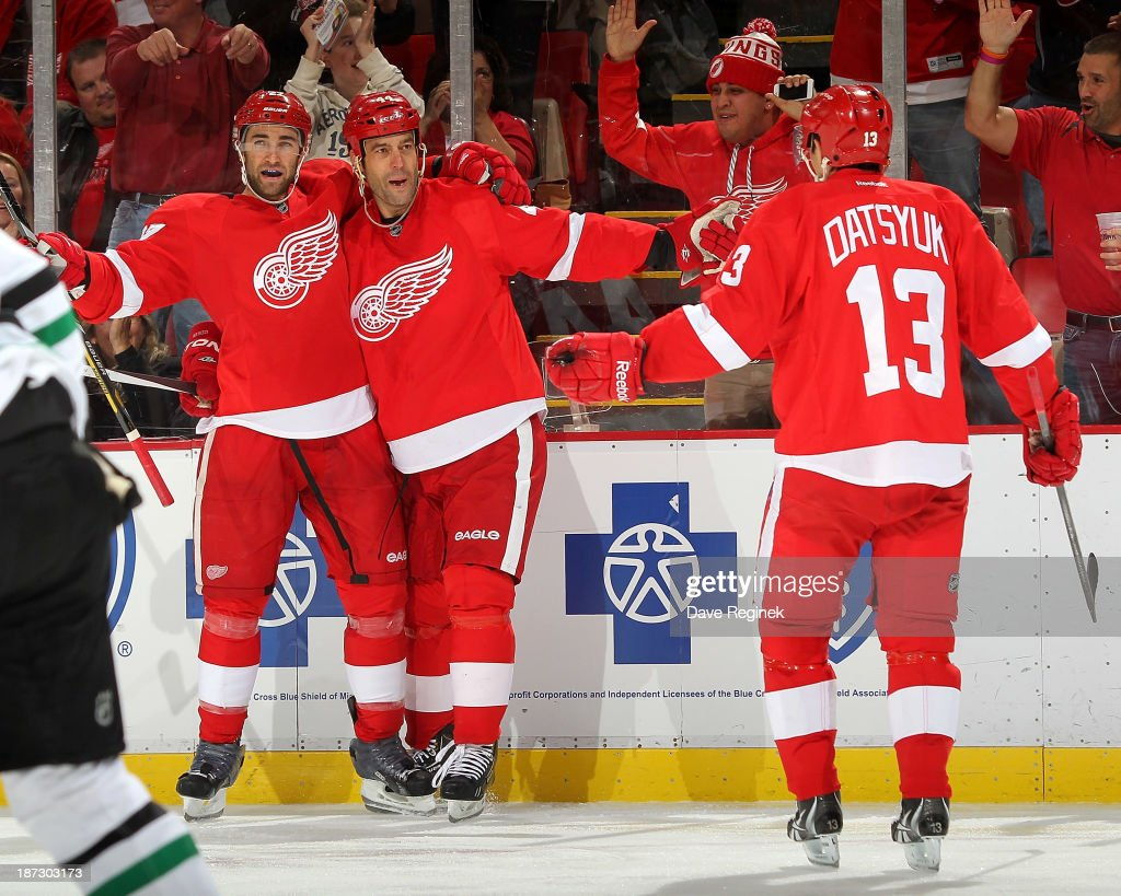 Kyle Quincey #27 and Pavel Datsyuk #13 of the Detroit Red Wings gather around teammate Todd Bertuzzi #44 after scoring a goal during an NHL game against the Dallas Stars at Joe Louis Arena on November 7, 2013 in Detroit, Michigan. Dallas defeated Detroit 4-3 in OT