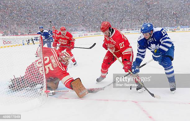 Kyle Quincey of the Detroit Red Wings battles for the puck against Joffrey Lupul of the Toronto Maple Leafs in front of goaltender Jimmy Howard of...