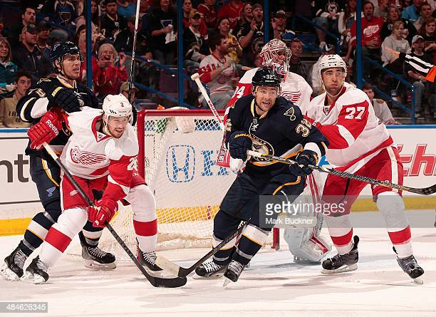 Kyle Quincey of the Detroit Red Wings shoves Chris Porter of the St Louis Blues out of the crease as Brendan Smith of the Detroit Red Wings defends...