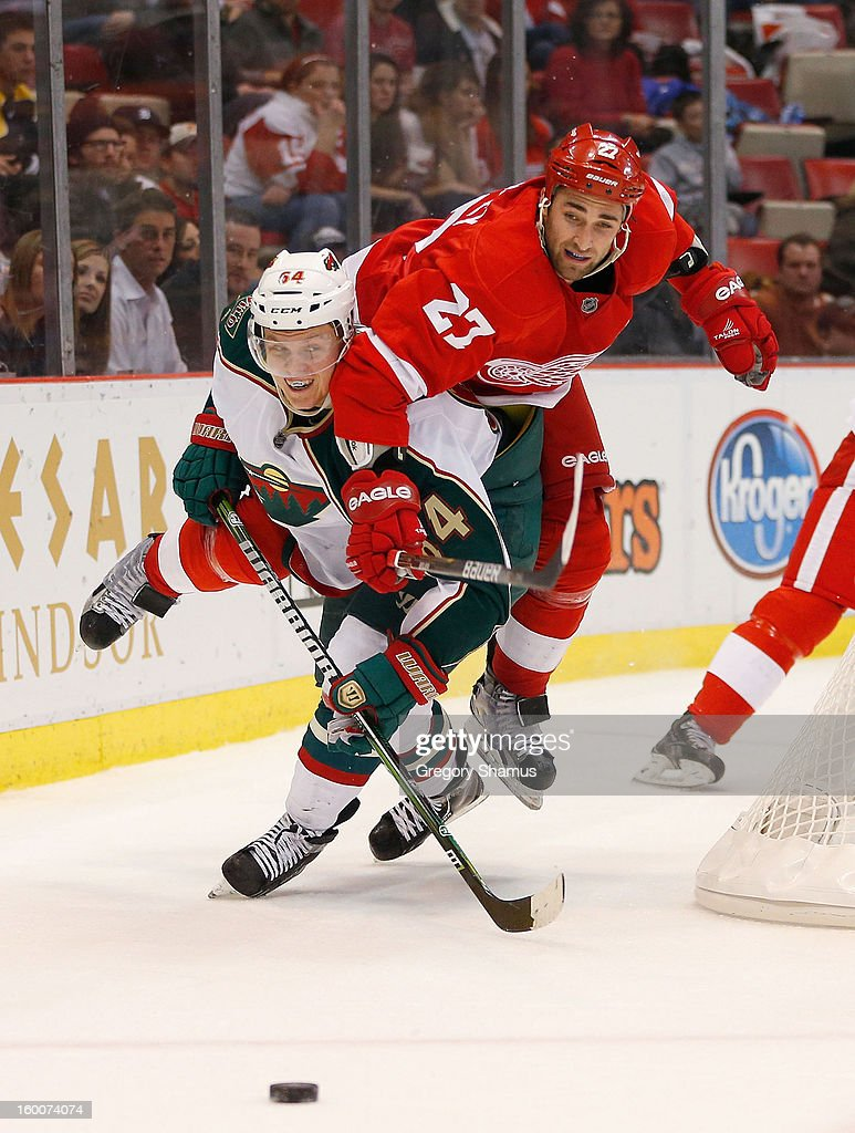 Kyle Quincey #27 of the Detroit Red Wings tries to jump over Mikael Granlund #64 of the Minnesota Wild to get to a third period puck at Joe Louis Arena on January 25, 2013 in Detroit, Michigan. Detroit won the game 5-3.