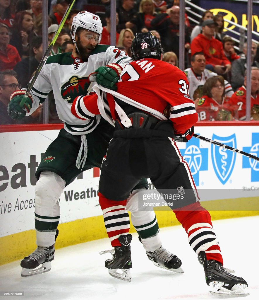 Kyle Quincey #27 of the Minnesota Wild and Ryan Hartman #38 of the Chicago Blackhawks tussle in the corner at the United Center on October 12, 2017 in Chicago, Illinois. The Wild defeated the Blackhawks 5-2.