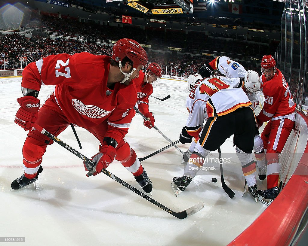 Kyle Quincy #27, Cory Emmerton #25 and Drew Miller #20 of the Detroit Red Wings battle for the puck along the boards with Roman Cervenka #10 and TJ Brodie #7 of the Calgary Flames during a NHL game at Joe Louis Arena on February 5, 2013 in Detroit, Michigan.