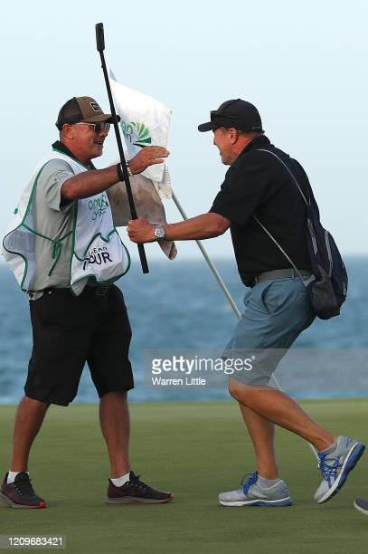 Kyle Roadley caddie to the victorious Sami Valimaki of Finland celebrates with fellow caddie Brian NIlsson during the final round of the Oman Open at...
