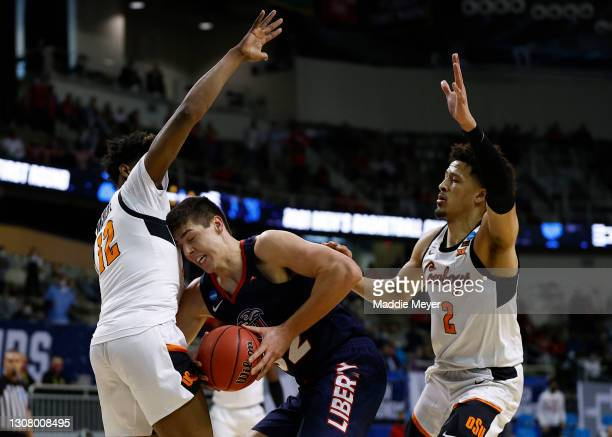 Kyle Rode of the Liberty Flames battles with Cade Cunningham of the Oklahoma State Cowboys and Matthew-Alexander Moncrieffe during the first half in...