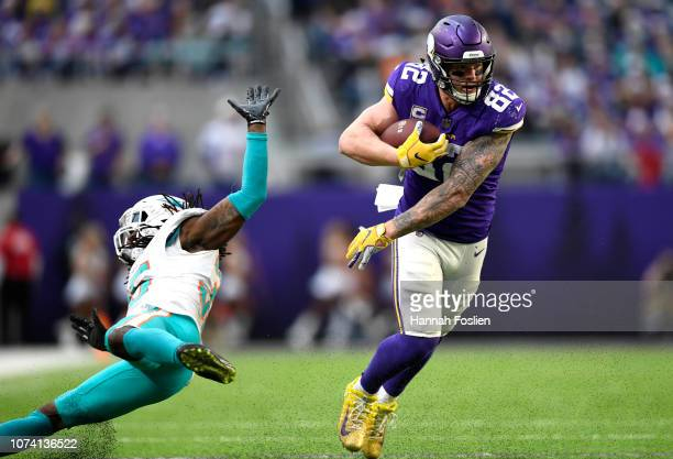 Kyle Rudolph of the Minnesota Vikings avoids a tackle by Walt Aikens of the Miami Dolphins in the third quarter of the game at US Bank Stadium on...