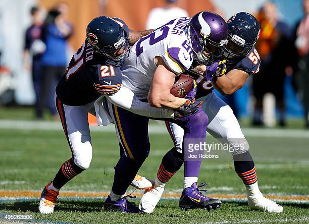 Kyle Rudolph of the Minnesota Vikings carries the football against Ryan Mundy and Jonathan Anderson of the Chicago Bears in the first quarter at...