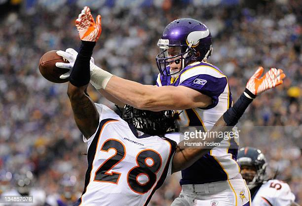 Kyle Rudolph of the Minnesota Vikings catches the ball over Quinton Carter of the Denver Broncos for a touchdown in the second quarter on December 4...